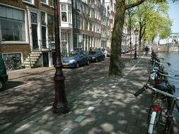 photo 'Biking along the  trees in Spring' and the canal-water in early May - c. 3 o'clock afternoon - location: Nieuwe Herengracht, in Amsterdam city.jpg
